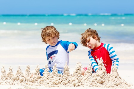 Two little kids boys having fun with building a sand castle on tropical beach of carribean island. children playing together on their vacations Twins, Happy brothers laughing and smiling. Reklamní fotografie