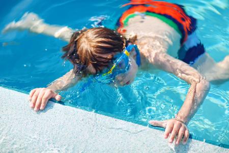 pequeño niño preescolar haciendo deporte de competición de natación. Niño con gafas de natación llegando al borde de la piscina. Niño divirtiéndose en una piscina. Niño feliz activo ganando. deportes, ocio activo. Foto de archivo