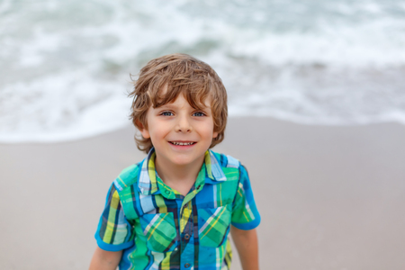 Adorable active little kid boy having fun on beach of North Sea in Germany. Happy cute child relaxing, playing and enjoying stormy warm day near palms and ocean. Kid with sand on funny beautiful face.