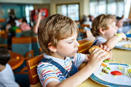 Cute healthy preschool kid boy eats hamburger sitting in school or nursery cafe. Happy child eating healthy organic and vegan food in restaurant. Childhood, health concept. Reklamní fotografie