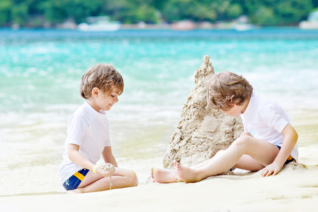 Two little kids boys having fun with building a sand castle on tropical beach of Seychelles. children playing together on their vacations