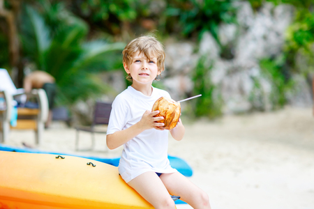 Happy funny little preschool kid boy drinking coconut juice on ocean beach. child playing on family vacations on tropical island. summer, happiness, childhood concept. Reklamní fotografie
