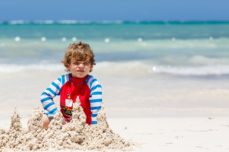 Adorable little blond kid boy having fun on tropical beach of carribean island. Excited child playing and building sand castle in sun protected swimsuit in ocean on vacations Reklamní fotografie