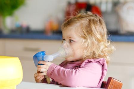 Klein peutermeisje dat thuis inhaleert met vernevelaar. Vader of moeder die het apparaat helpt en vasthoudt. Kind met griep, hoest en bronchitis. astma-inhalator inademing stoom ziek concept