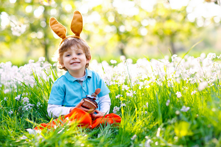 Cute little kid boy with Easter bunny ears celebrating traditional feast. Happy child eating chocolate cake of muffin on warm sunny day. Family, holiday, spring concept. Toddler sitting on grass.