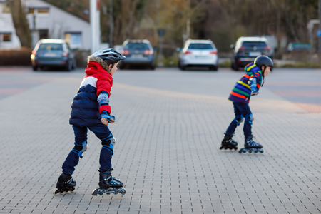 Two little kids boys skating with rollers in the city. Happy children, siblings and best friends in protection safety clothes. Active schoolboys making sports and learning to skate on inline skater. Reklamní fotografie
