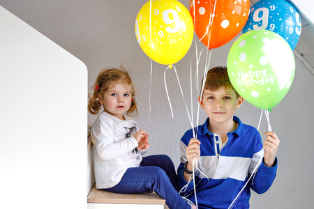 Portrait of happy kid boy and cute little toddler girl with bunch on colorful air balloons on birthday. Smiling happy school child and sister having fun, celebrating birthday. Family party Reklamní fotografie