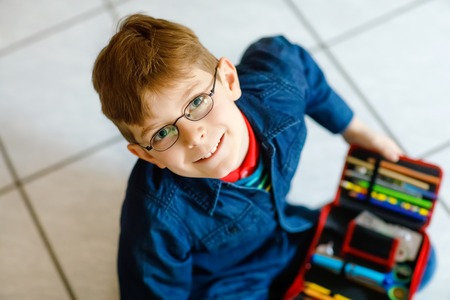 Glücklicher kleiner Schuljunge, der nach einem Stift im Federmäppchen sucht. Gesundes Schulkind mit Brillengriff denkt für den Unterricht in der Grundschule.