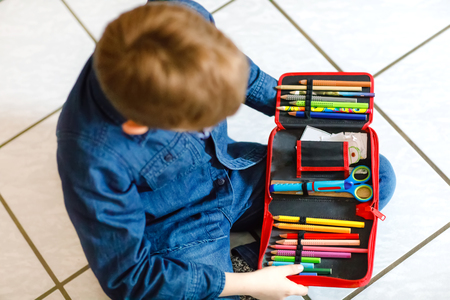 Happy little school kid boy searching for a pen in pencil case. Healthy schoolchild with glasses grab thinks for lessons in elementary class. Reklamní fotografie