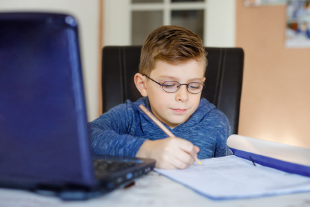 Happy healthy kid boy with glasses making school homework at home with notebook. Interested child writing essay with helping of internet. concetrated schoolchildren concept