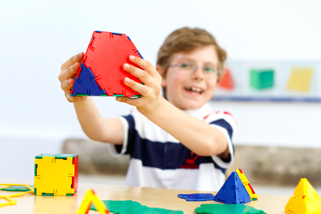 Happy kid boy with glasses having fun with building and creating geometric figures, learning mathematics and geometry Reklamní fotografie