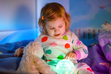 Cute little toddler girl playing with colorful night light lamp before going to bed. Sleepy tired baby daughter in nightwear having fun. Healthy child not sleeping.