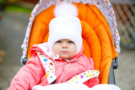 Cute little beautiful baby girl sitting in the pram or stroller on autumn day. Happy healthy child going for a walk on fresh air in warm clothes. Baby with yellow fall maple trees in colorful clothes