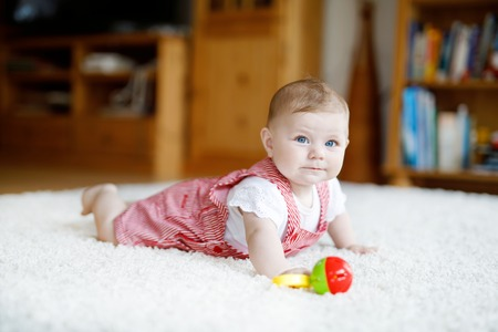Cute baby playing with colorful rattle education toy. Lttle girl looking at the camera and crawling. Family, new life, childhood, beginning concept. Baby learning grab.