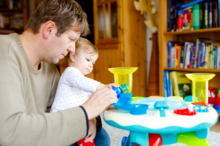Happy proud young father having fun with baby daughter, family portrait together. Dad playing with baby girl with educational sorter toy with different colorful balls. Man with little child at home.