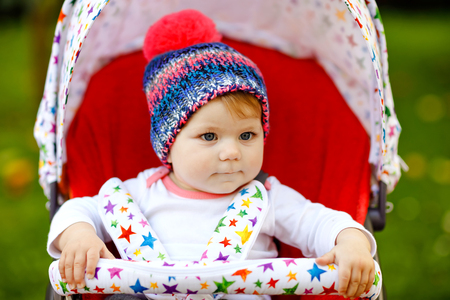 Cute healthy little beautiful baby girl with blue warm hat sitting in the pram or stroller and waiting for mom. Happy smiling child with blue eyes. baby daughter going for a walk with family. Reklamní fotografie