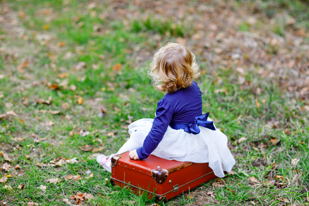 Cute little toddler girl sitting on suitcase in autumn park. Happy healthy baby enjoying walking with parents. Sunny warm fall day with child. Active leisure and activity with kids in nature