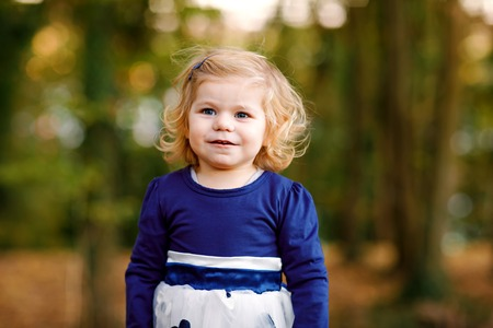 Cute little toddler girl making a walk through autumn park. Happy healthy baby enjoying walking with parents. Sunny warm fall day with child. Active leisure and activity with kids in nature