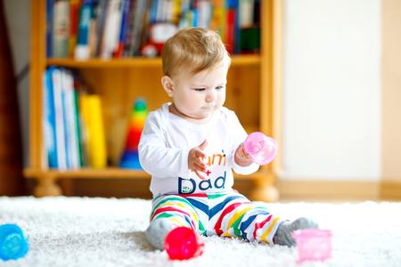 Entzückendes Baby, das mit Lernspielzeug im Kindergarten spielt. Glückliches gesundes Kind, das zu Hause Spaß mit bunten verschiedenen Spielsachen hat. Babyentwicklung und erste Schritte, Spielen und Greifen lernen Standard-Bild