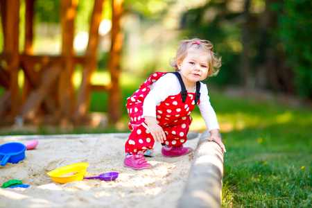 Cute toddler girl playing in sand on outdoor playground. Beautiful baby in red gum trousers having fun on sunny warm summer day. Child with colorful sand toys. Healthy active baby outdoors plays games Banque d'images - 121691643