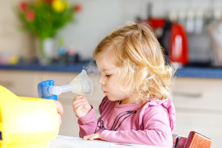 Little toddler girl making inhalation with nebulizer at home. Father or mother helping and holding the device. Child having flu, cough and bronchitis. asthma inhaler inhalation steam sick concept