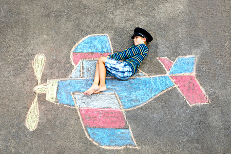 Little kid boy having fun with with airplane picture drawing with colorful chalks on asphalt. Child painting with chalk and crayon and going on vacations or dreaming of pilot profession. Archivio Fotografico