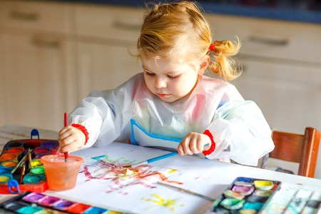 Cute adorable baby girl learning painting with water colors. Little toddler child drawing at home, using colorful brushes. Healthy happy daughter experimenting with colors, water at home or nursery Reklamní fotografie