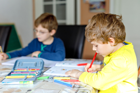 Two little kids boys at home making homework. Little concentrated children writing with colorful pencils, indoors. Elementary school and education. Siblings and best friends learning. Reklamní fotografie