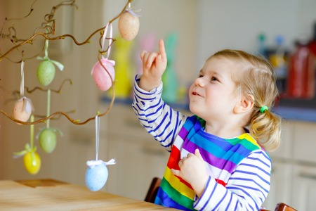 Cute little toddler girl decorating tree bough with colored pastel plastic eggs. Happy baby child having fun with Easter decorations. Adorable healthy smiling kid in enjoying family holiday