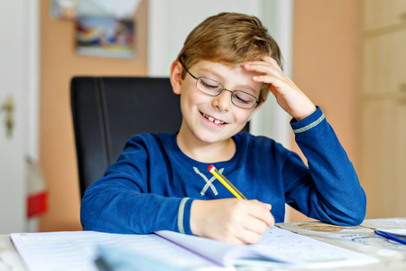 Portrait of cute school kid boy wearing glasses at home making homework. Little concentrated child writing with colorful pencils, indoors. Elementary school and education