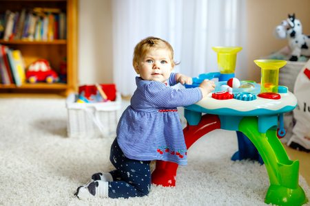 Adorable cute beautiful little baby girl playing with educational toys at home or nursery. Happy healthy child having fun with colorful different toys. Kid learning different skills.