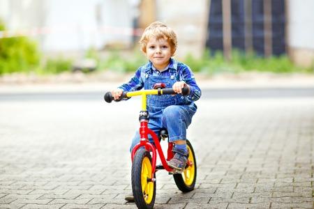 Aktiver blonder Junge in bunten Kleidern, der Balance fährt und Lernende Fahrrad oder Fahrrad im Hausgarten fährt. Kleinkind träumt und hat Spaß an einem warmen Sommertag. Bewegungsspiel im Freien für Kinder