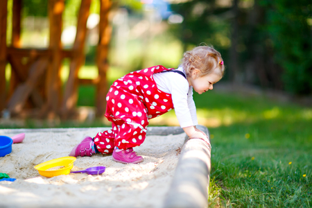 Cute toddler girl playing in sand on outdoor playground. Beautiful baby in red gum trousers having fun on sunny warm summer day. Child with colorful sand toys. Healthy active baby outdoors plays games