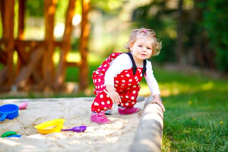 Nettes Kleinkindmädchen, das im Sand auf Spielplatz im Freien spielt. Schönes Baby in roten Gummihosen, die sich an einem sonnigen, warmen Sommertag amüsieren. Kind mit bunten Sandspielzeugen. Gesundes aktives Baby im Freien spielt Spiele