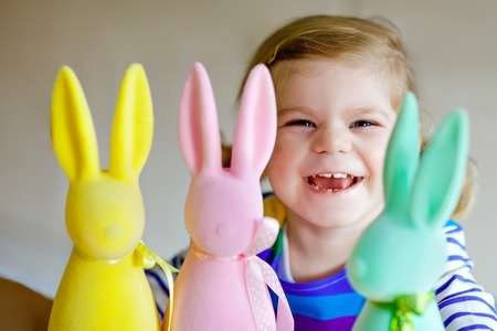 Cute little toddler girl with three colored pastel bunnies Happy baby child having fun with Easter decorations bunny in pink, yellow and green. Adorable healthy smiling kid in enjoying family holiday