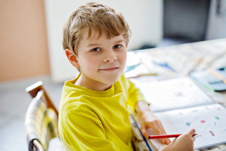 Portrait of cute school kid boy at home making homework. Little concentrated child writing with colorful pencils, indoors. Elementary school and education. Kid learning writing letters and numbers.