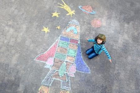 Niño divertido niño volando en el universo por una pintura de imagen del transbordador espacial con tizas de colores. Ocio creativo para niños al aire libre en verano