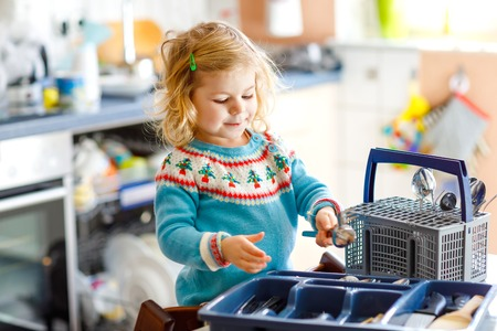 Cute little toddler girl helping in the kitchen with dish washing machine. Happy healthy blonde child sorting knives, forks, spoons, cutlery. Baby having fun with helping housework mother and father. Banque d'images