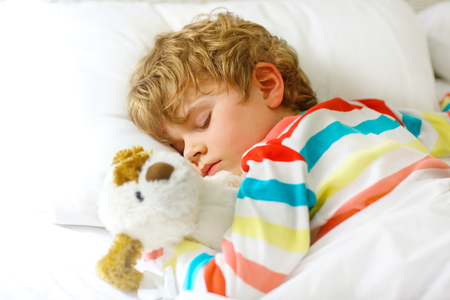 Adorable little blond kid boy in colorful nightwear clothes sleeping and dreaming in his white bed with toy. healthy child with soft toy, peaceful sleep at home