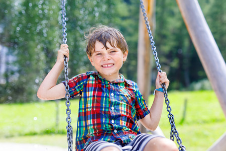 Funny kid boy having fun with chain swing on outdoor playground during rain. child swinging on warm rainy summer day. Active leisure with kids. Happy boy with rain drops on face. Stock Photo