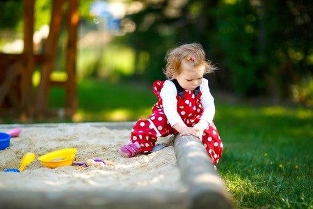 Cute toddler girl playing in sand on outdoor playground. Beautiful baby in red gum trousers having fun on sunny warm summer day. Child with colorful sand toys. Healthy active baby outdoors plays games Banque d'images - 121029408