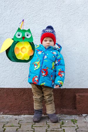 Little kid boy holding selfmade lanterns for a Halloween or St. Martin procession. Beautiful healthy cute child happy about children and family parade in kindergarten. German tradition Martinsumzug Фото со стока