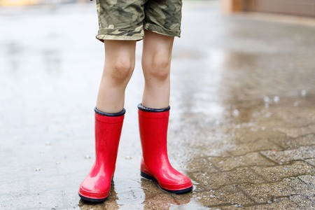Child wearing red rain boots jumping into a puddle. Close up. Kid having fun with splashing with water. Warm heavy summer rain and happy children. Foto de archivo - 121029467