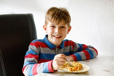 Cute healthy schoolkid boy eats pasta noodles sitting in school or nursery cafe. Happy child eating healthy organic and vegan food in restaurant or at home. Childhood, health concept