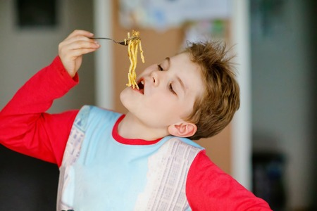 Cute healthy preschool kid boy eats pasta noodles sitting in school or nursery cafe. Happy child eating healthy organic and vegan food in restaurant or at home. Childhood, health concept