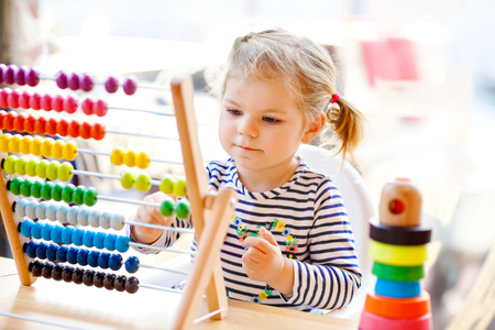 Adorable cute beautiful little toddler girl playing with educational wooden rainbow toy pyramid and counter abacus. Healthy happy baby learning to count and colors, indoors on sunny day. Stock Photo
