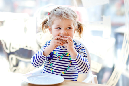 Cute little adorable toddler girl sitting in indoor cafe restaurant. Happy healthy baby child eating bread or sweet scone on sunny day. Imagens
