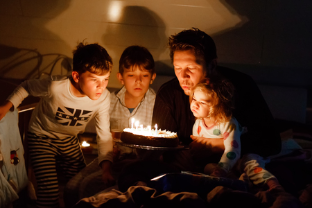 Three children, toddler girl and two school kids boys congratulating father to his birthday. Baby sister child, two brothers and dad with cake blowing candles. Happy healthy family portrait. Stockfoto