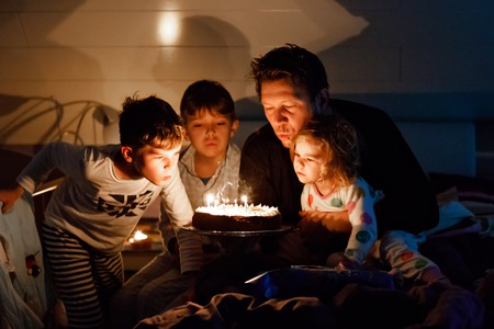 Three children, toddler girl and two school kids boys congratulating father to his birthday. Baby sister child, two brothers and dad with cake blowing candles. Happy healthy family portrait. 版權商用圖片
