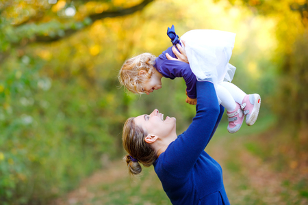 Happy young mother having fun cute toddler daughter, family portrait together. Woman with beautiful baby girl in nature and forest. Mum with little child outdoors, hugging. Love, bonding. Stock Photo